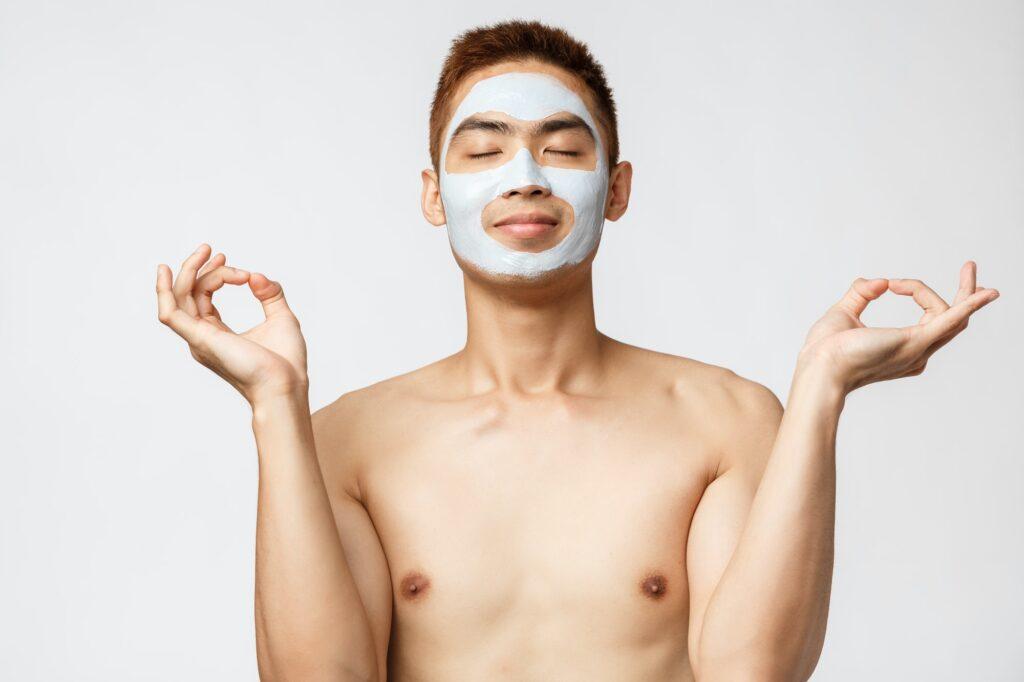 Beauty, skincare and spa concept. Portrait of relaxed and calm naked asian guy, meditating while