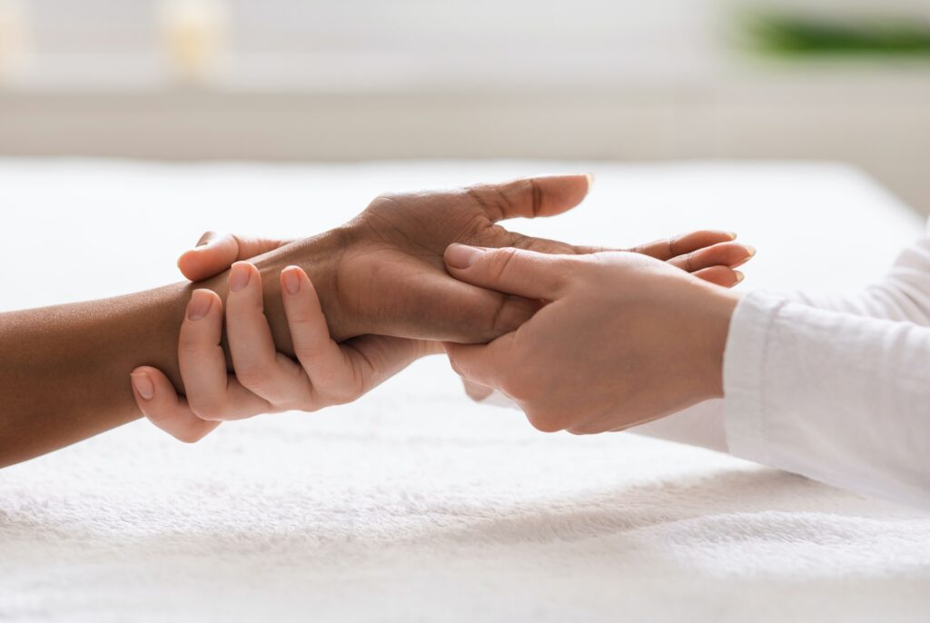 Masseuse giving professional hand massage at spa