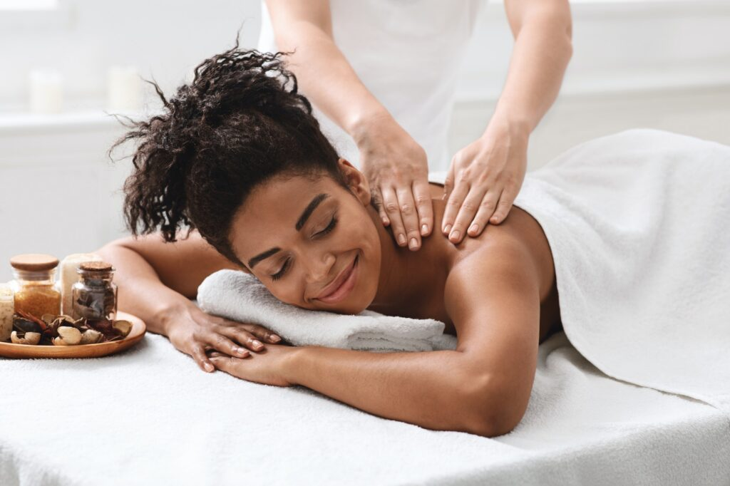 Peaceful african girl having body massage with aromatherapy
