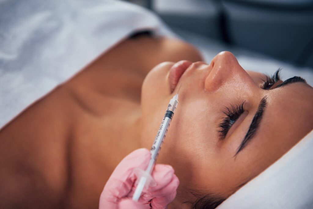 Woman lying down in spa salon and have injection by the syringe into her face skin